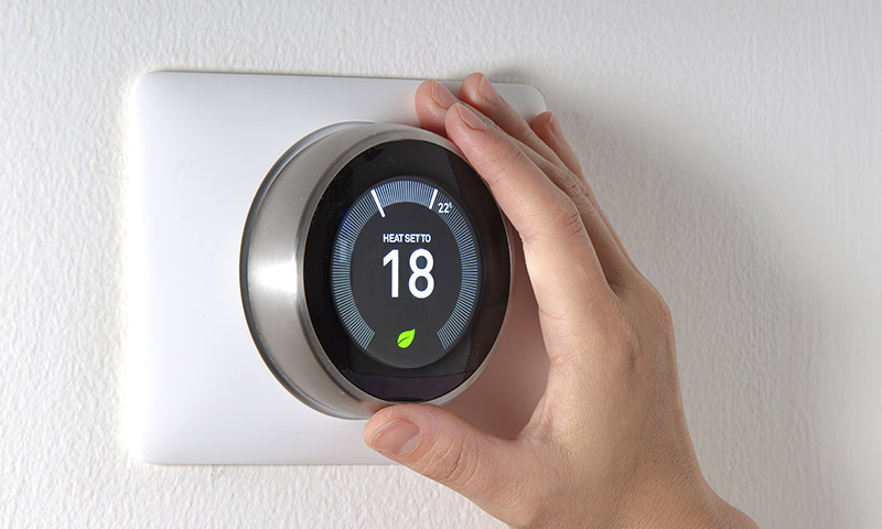 Person adjusting their smart thermostat