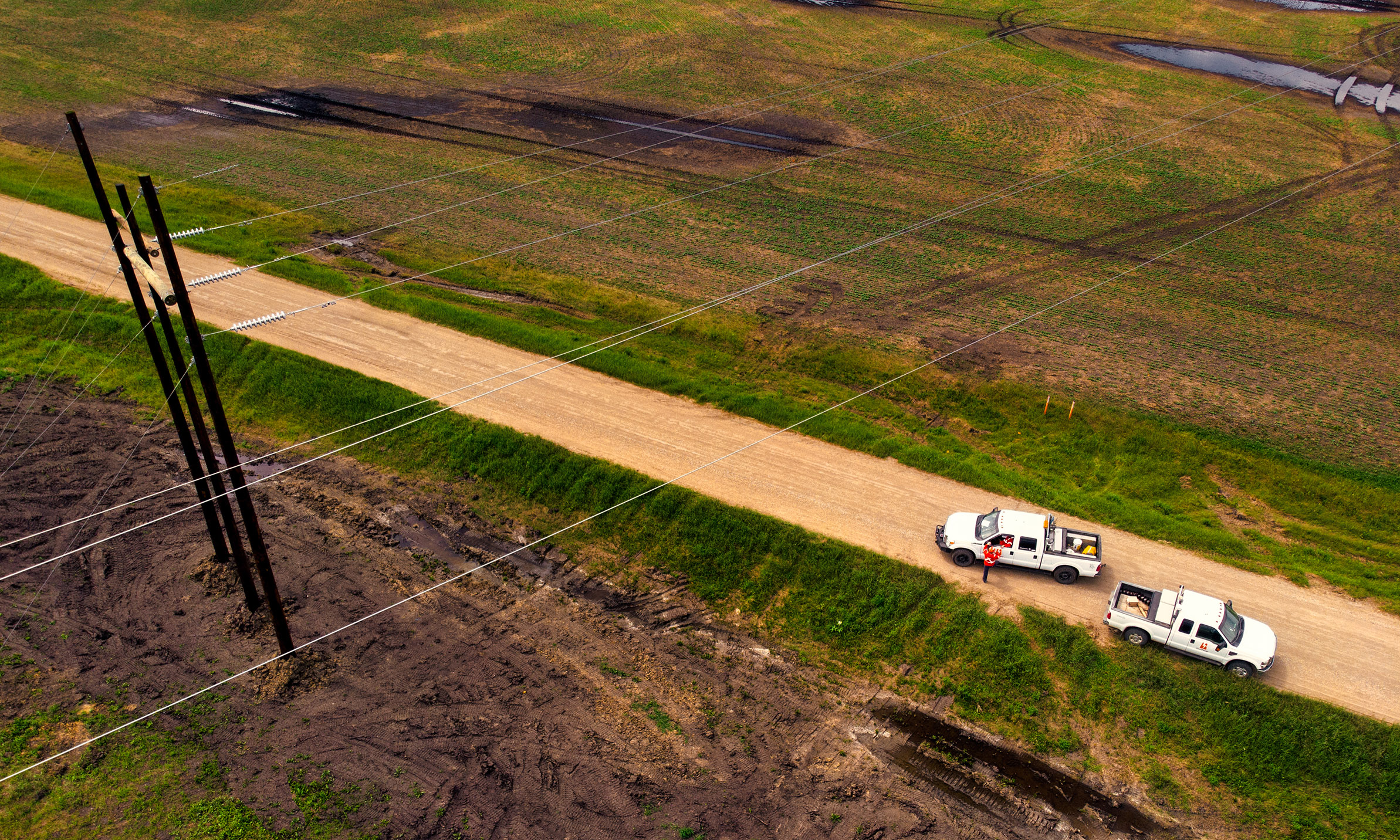 Ariel view of transmission lines with 2 SaskPower trucks on a grid road